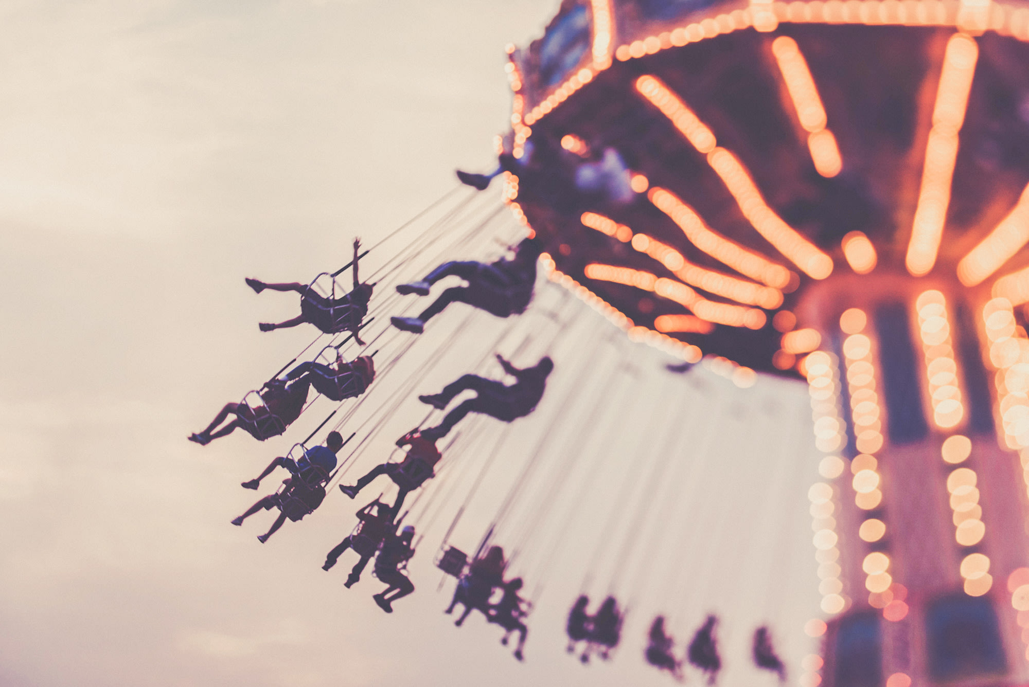 People hanging from a fairground ride.