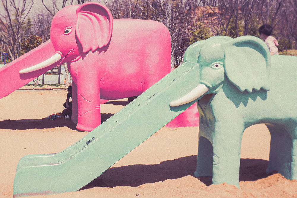 Playground equipment shaped like elephants with slides for trunks.