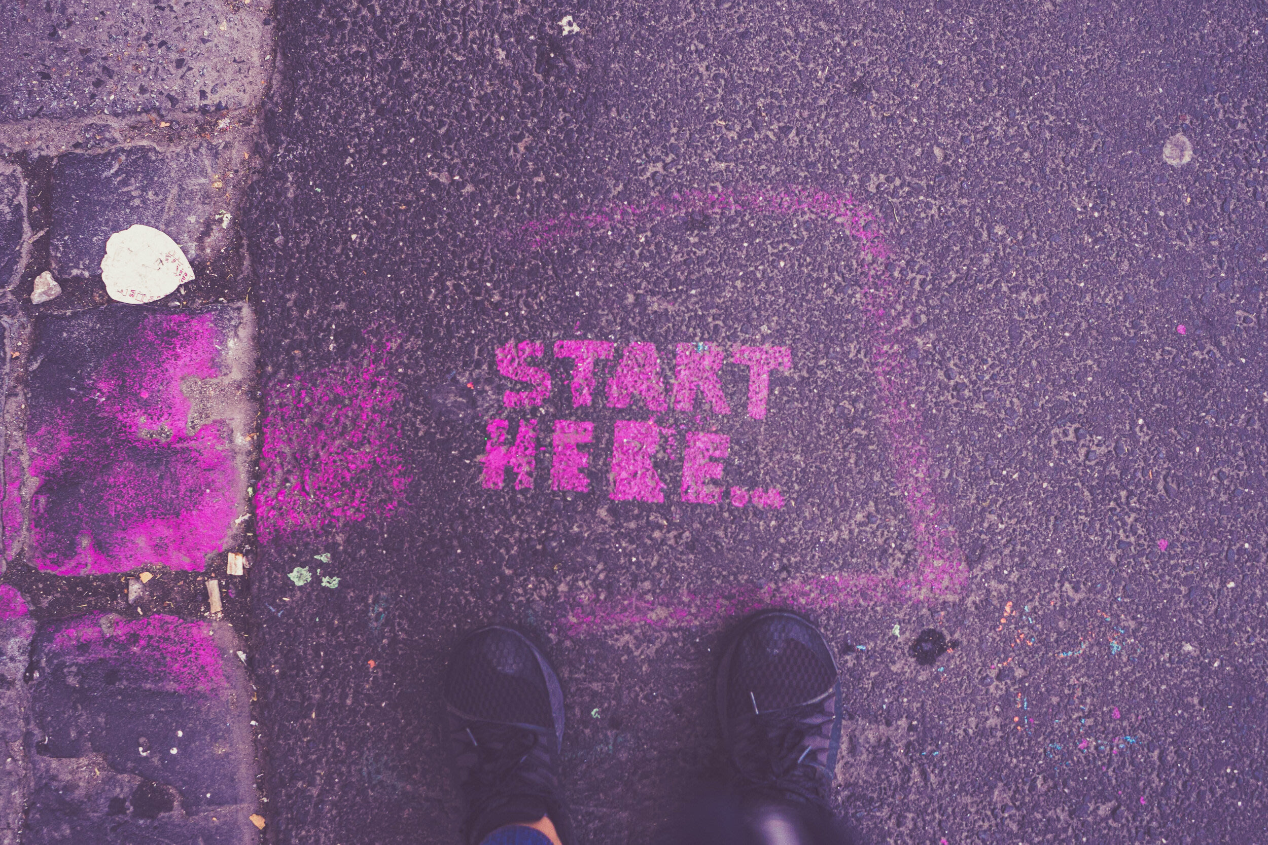 The words 'start here' written on the pavement.