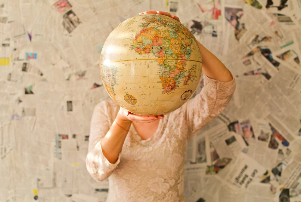 A person holding a world globe in front of their face.