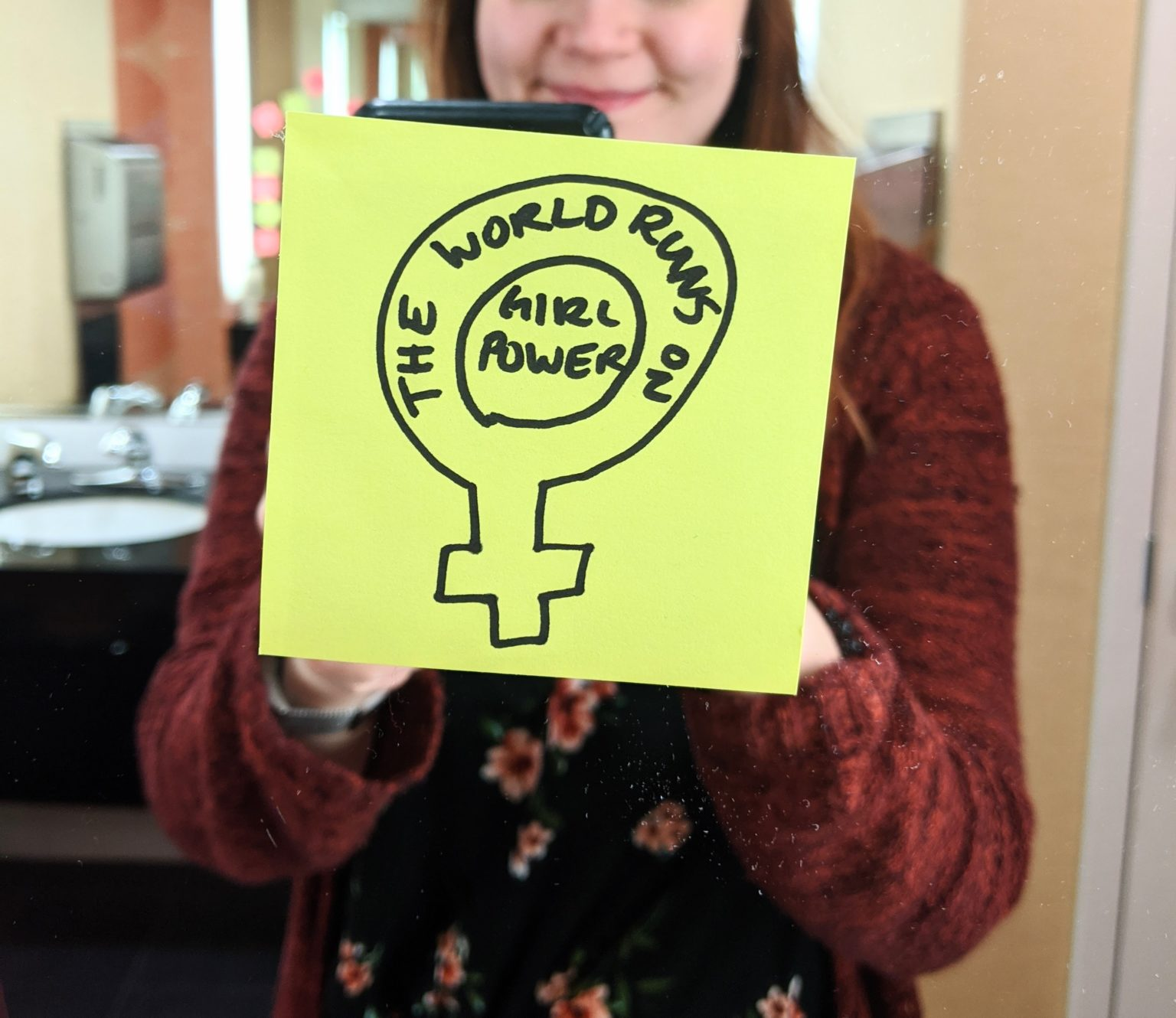 "Sticky note on mirror that says: ""The world runs on girl power"""