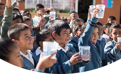 Kinder halten Tassen mit sauberem Wasser