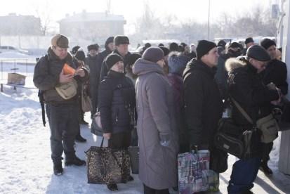 Люди на холоде стоят в очереди, чтобы пересечь «линию разграничения». (Фотография сделана в начале пандемии COVID-19).