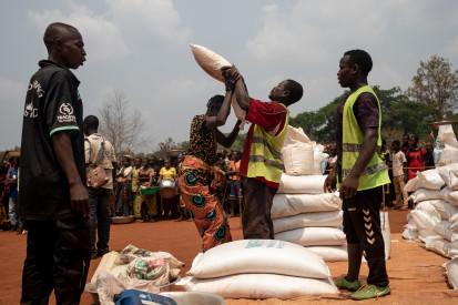 Une femme déplacée se fait donner un sac de nourriture lors d'une distribution de vivres du Programme alimentaire mondial sur le site de déplacés internes de Siwa. ©OCHA/Adrienne Surprenant, Bangassou, Préfecture du Mbomou, RCA, 2021.