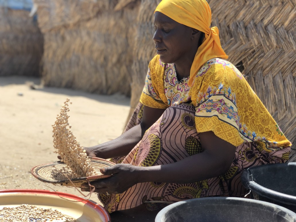 IDP woman sorting grains in front of her shelter in Custom House camp, Maiduguri