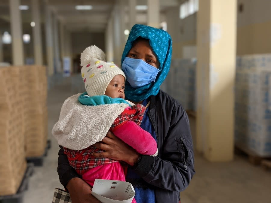 Mirat holding her 5-month-old baby during a UNHCR/WFP food distribution (OCHA/Jennifer Bose Ratka)
