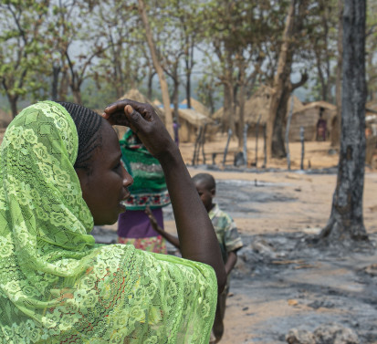Burned to the ground by recent clashes, Fatima looks into the direction of where her hut used to be. ©OCHA/Anita Cadonau, Bambari, Ouaka Prefecture, CAR, 2021.
