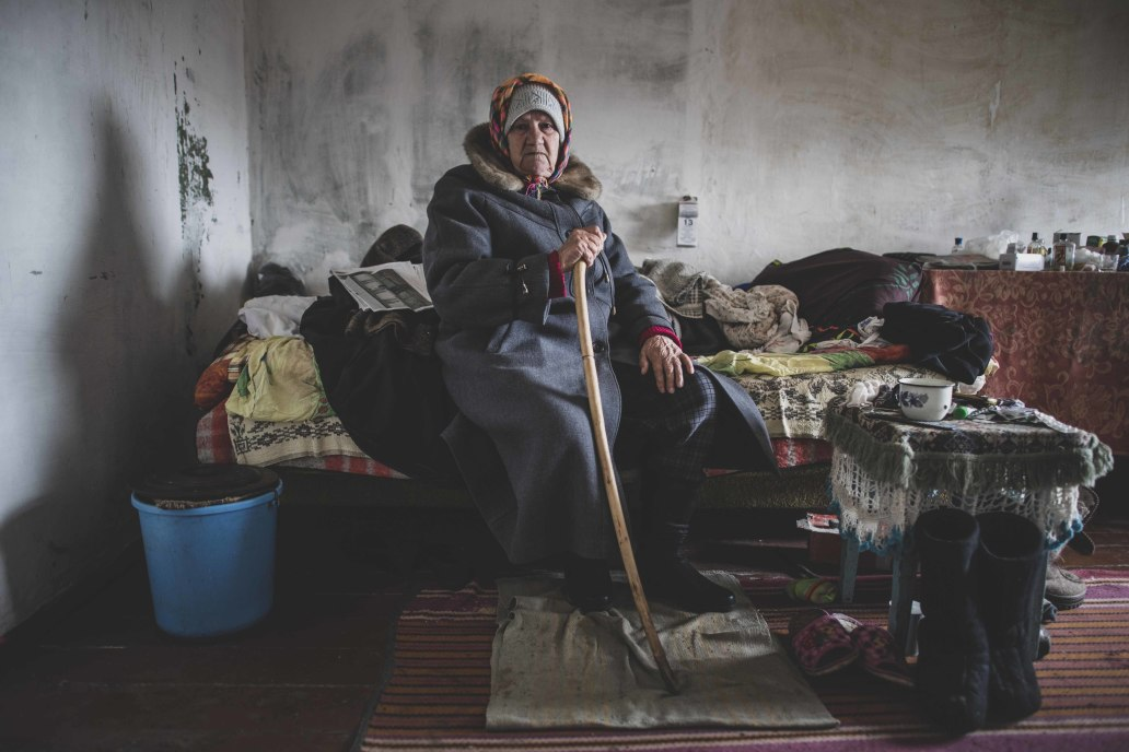 An older woman dressed in layers sits on her bed in a partially damaged house, trying to stay warm in winter