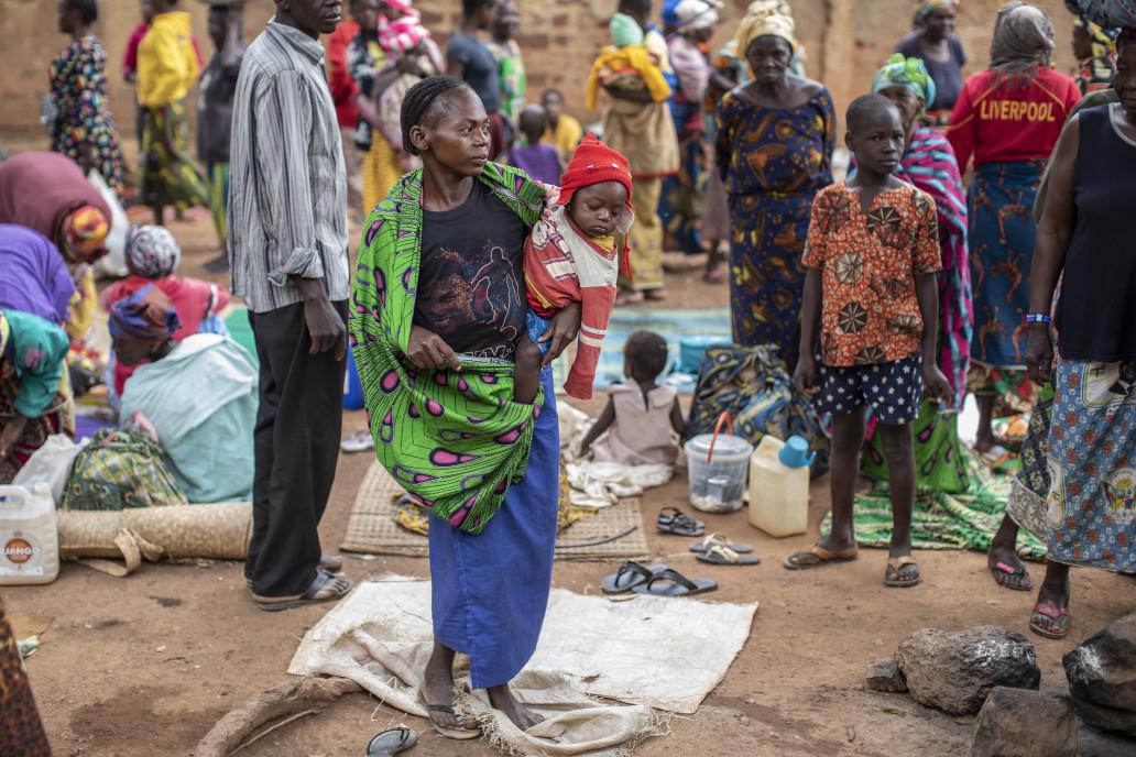 Mwala Georgette, 24 ans, tient son petit garçon, Kuri Isai, âgé de neuf mois, près d'une église utilisée pour abriter les familles déplacées en raison de la dernière vague de troubles dans la capitale Bangui.  ©OCHA/Siegfried Modola, Bangui, RCA, 2021.