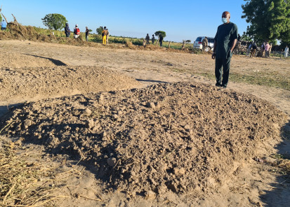Resident and Humanitarian Coordinator standing before mass grave