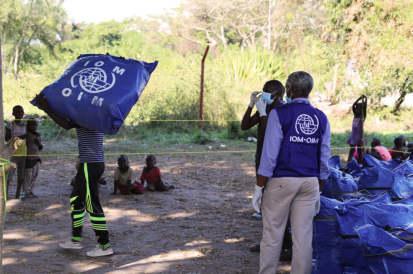Le personnel de l'OIM distribue des kits d'ANA aux victimes des inondations de Gatumba tout en respectant les mesures de prévention COVID-19. ©Triffin Ntore, OIM Burundi