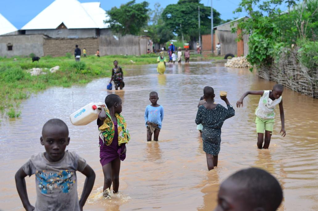 Les enfants traversent leur village à Gatumba pour se rendre à la route principale, où les familles sont rassemblées avec leurs biens restants, mais n'ont nulle part où aller, en avril 2020.  ©Lauriane Wolfe/OCHA 2020