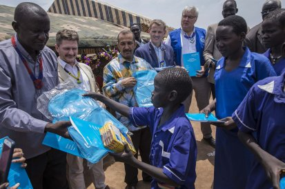 Caption: School children receive school bags, books and other school materials in Aweil town. More than 75,000 children will be reached by the joint programme on education in emergencies. Credit: UNICEF