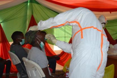 Un des médecins de l'équipe d'intervention rapide, EIR,  fait le dépistage d'un jeune garçon présentant des symptômes sur le site érigé au terrain ETS Kamenge, ©OCHA Burundi/Annick juillet 2020