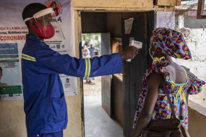 Un employee prend la température d'une patiente avant qu'elle entre dans l'Hôpital de Bimbo près de la capitale Bangui où l'ONG ALIMA met en œuvre un projet de prévention et prise en charge de la COVID-19. ©OCHA/Siegfried Modola, Bangui, RCA, 2021.