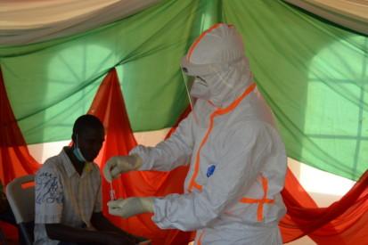 Le personnel de l'Equipe d'intervention rapide, EIR,  s'apprête à faire le dépistage d'un homme présentant des symptômes sur le site érigé au terrain ETS Kamenge, ©OCHA Burundi/Annick juillet 2020