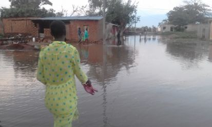 A Burundian woman walks through the flooded streets of her neighborhood. © Patient Munezero