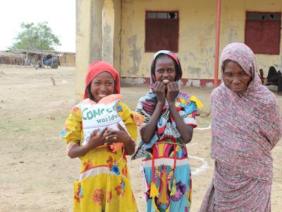 طيبة مع جدتها وصديقتها في مركز توزيع بذور التقاوي بولاية غرب كردفان (منظمة كونسيرن - حول العالم، يونيو 2020)