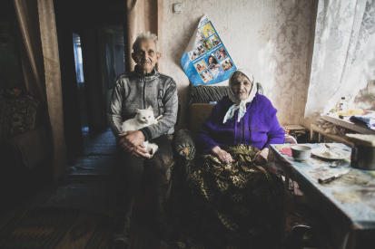 """A family is sitting in their house close to the """"contact line"""". Photo: OCHA/Yevhen Maloletka"""