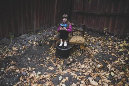 Дівчинка сидить на подвір'ї свого дому, який знаходиться на «лінії розмежування»