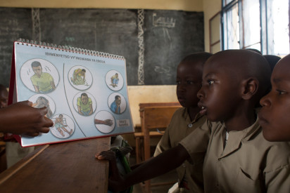 Burundian children are taught about good hygiene practices using an image kit. UNICEF 2019 / KAREL PRINSLOO