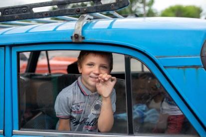 Мальчик в машине ждет отца, который покупает гигиенические средства с помощью ваучера, предоставленного гуманитарной организацией.