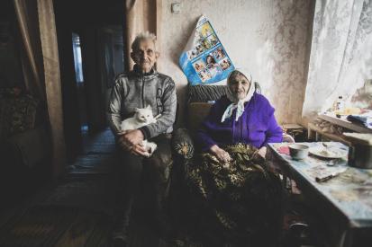 Cім'я сидить у своєму будинку, який знаходиться на «лінії розмежування». Фото: УКГС ООН/Євген Малолетка