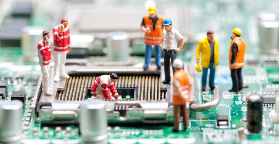 <p>Miniature models of people working on a circuit board</p>