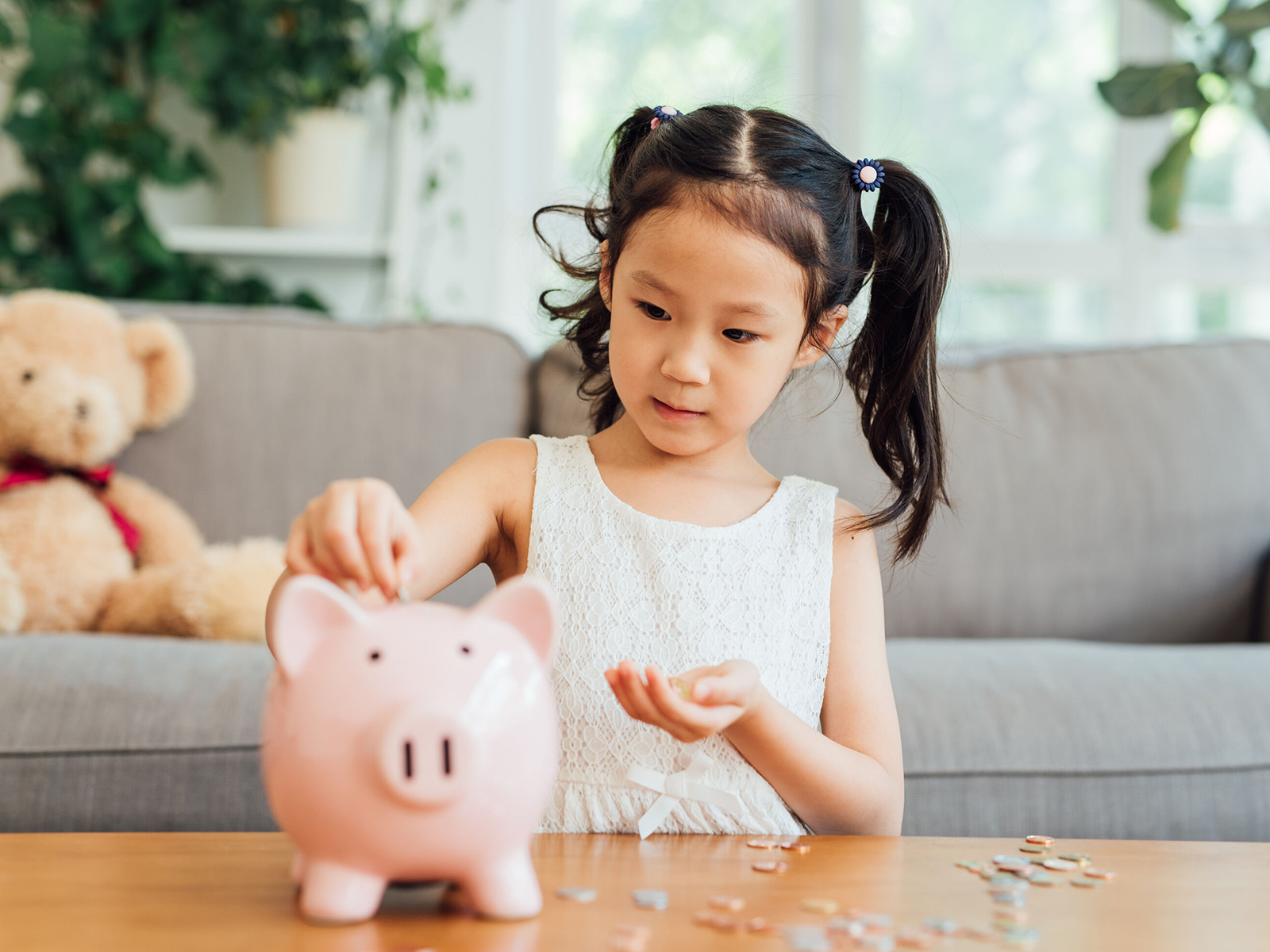 little girl slots coins into her piggy bank