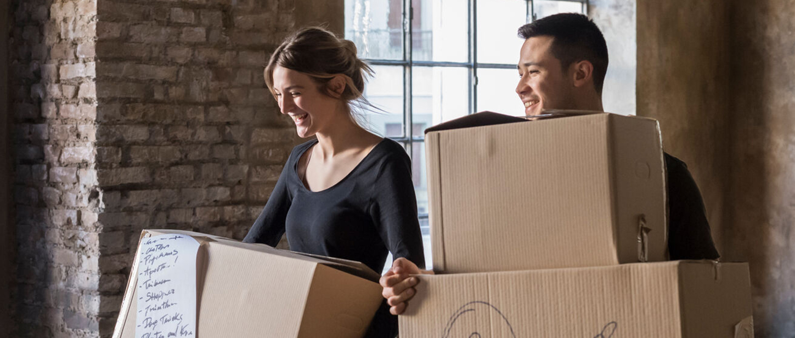 Young couple carries moving boxes into their new home