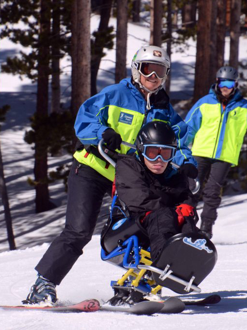 Handicapped skier and his adaptive sports coach skiing down a mountain