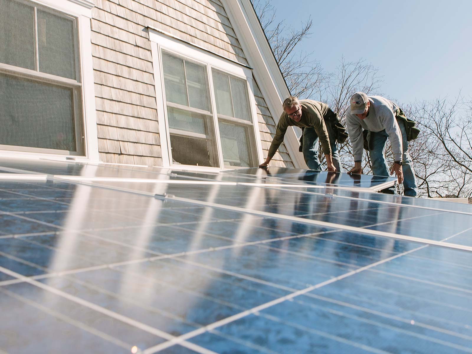 Two workers install solar panels on the roof of a suburban home