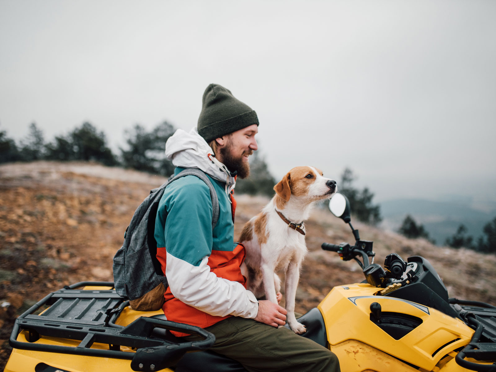 Man on an ATV with a dog sitting on his lap