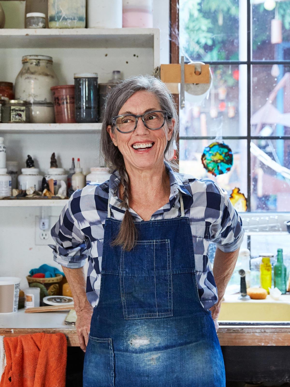 Vertical - Female artist with gray side braid and glasses in a blue apron sitting in front of her studio workbench
