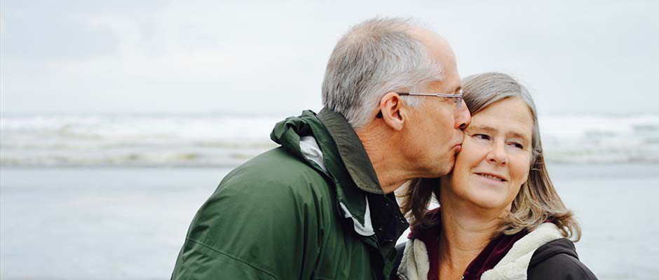Retired couple embracing on the beach