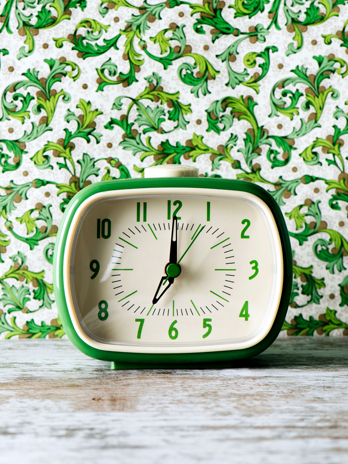 A green clock in front of a green floral print wallpapered wall