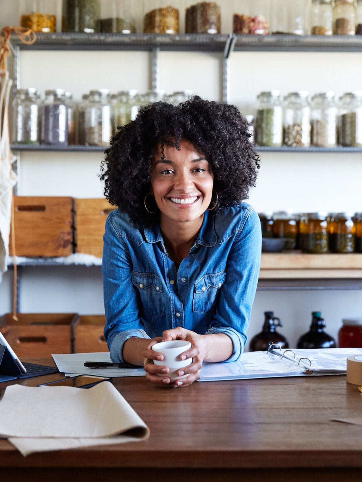 Woman leaning on desk and smiling in her skincare studio