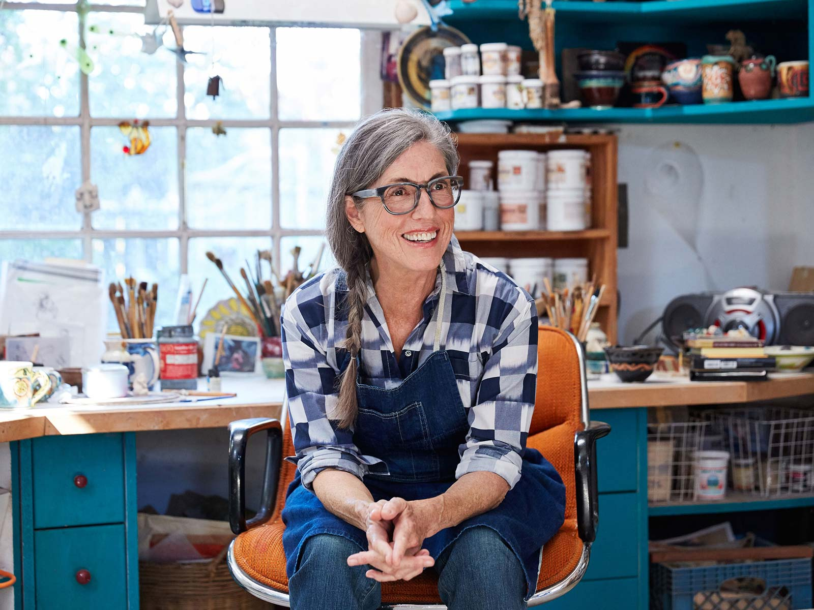 Female artist with gray side braid and glasses in a blue apron sitting in front of her studio workbench