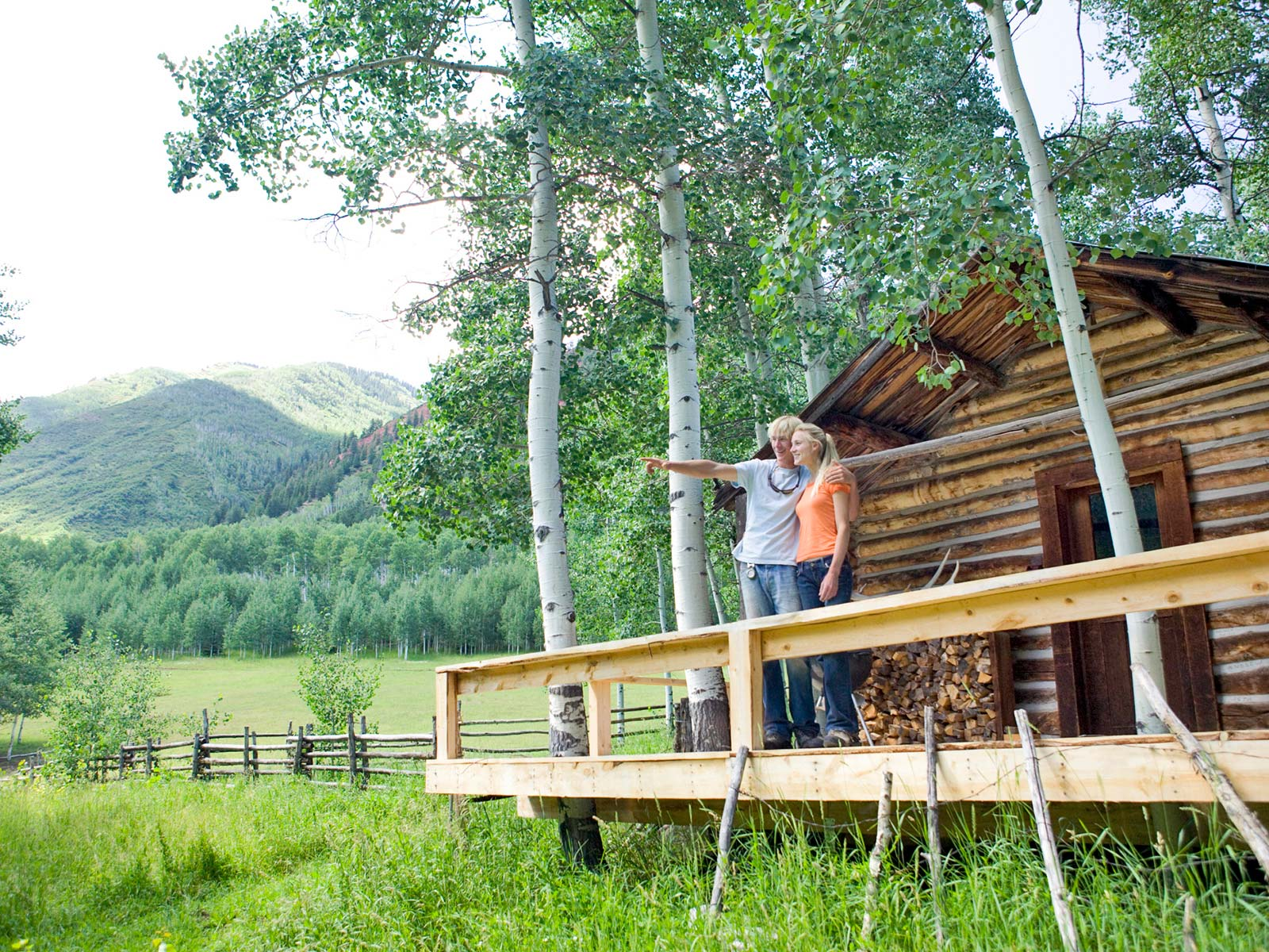 Couple standing on the porch of their log cabin viewing mountain scenery