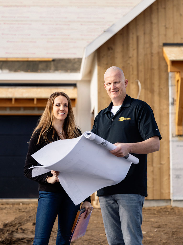 A man and woman looking at architectural plans in front of a home under construction