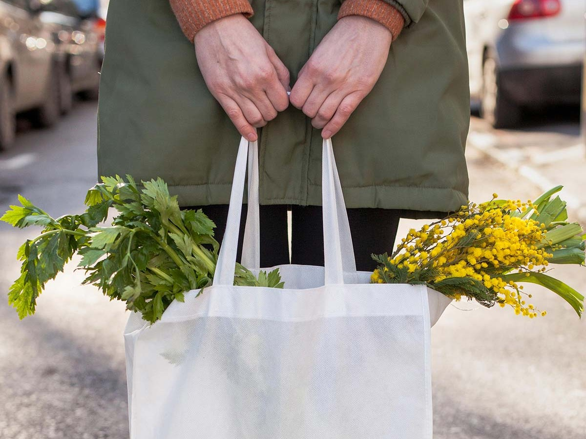 Horizontal - A woman standing in the street with focus on a bag of vegetables and flowers