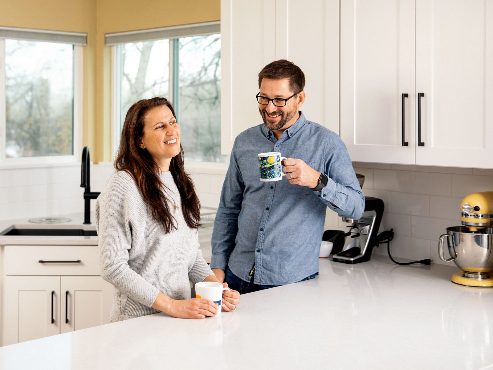 Horizontal image of Man and woman making coffee in a renovated kitchen