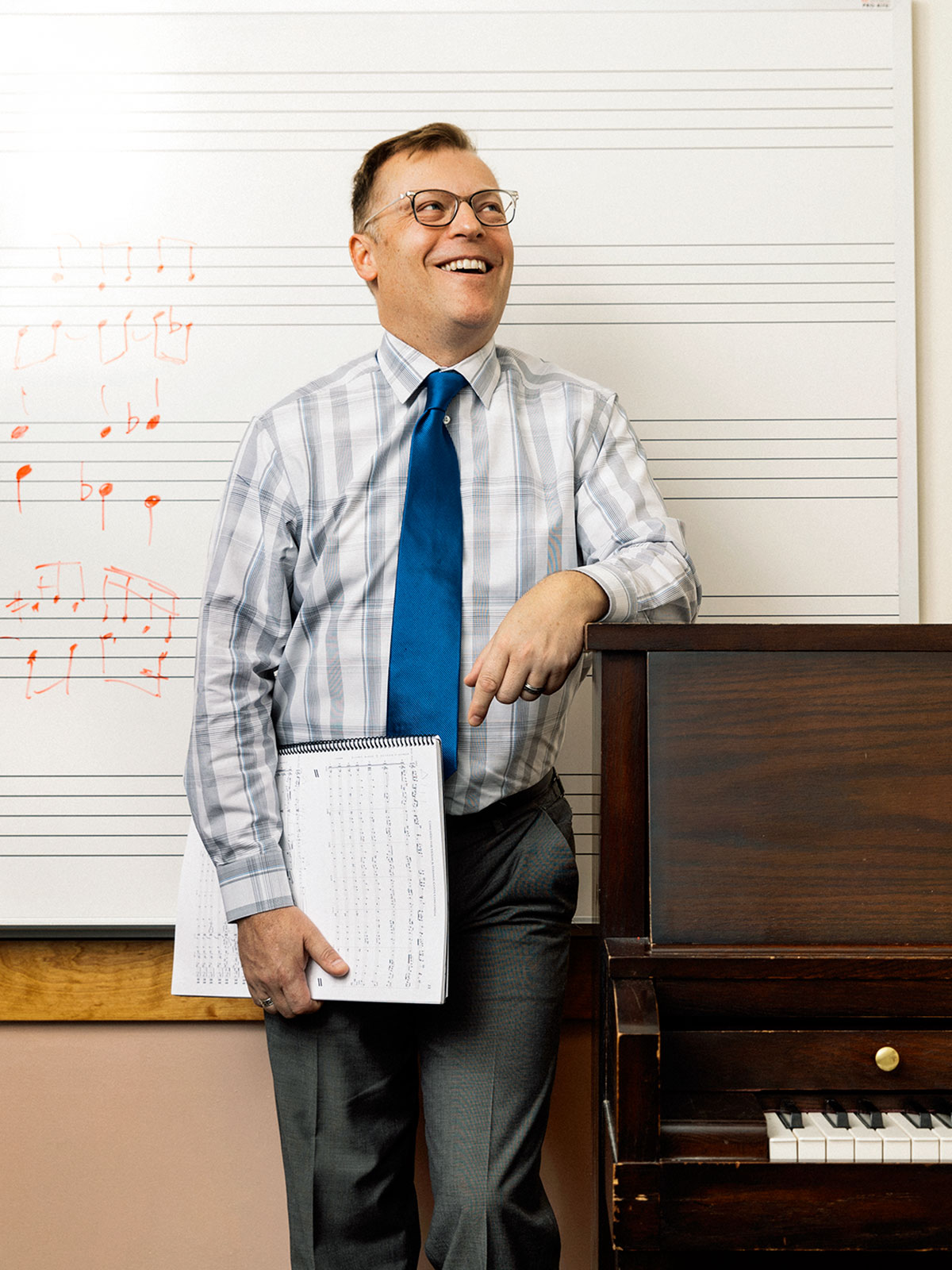 A music professor stands in front of the piano with music written on the a board behind him