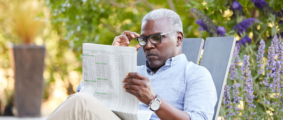 Man reading a business newspaper outdoors