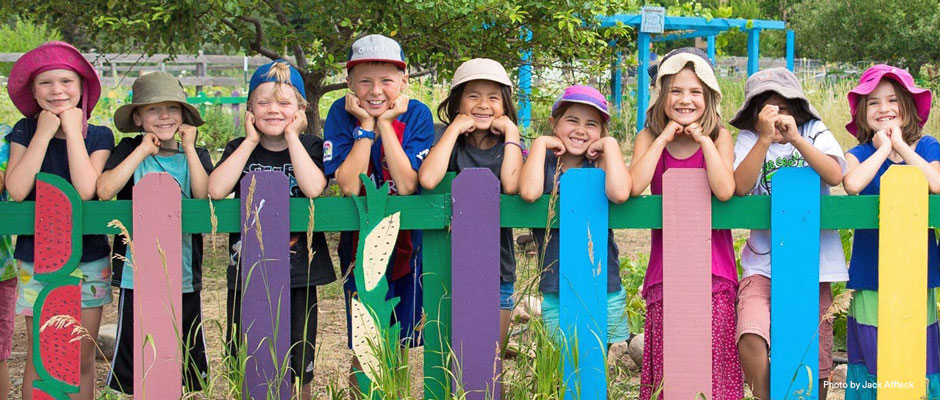 Children smiling leaning on a colorful painted fence in front of a playground - 940x400