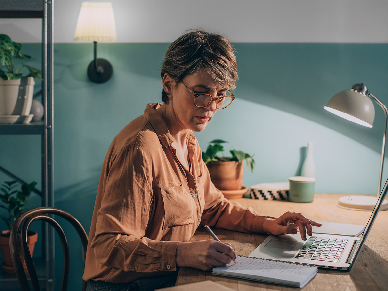 Woman working at her desk in front of a laptop computer