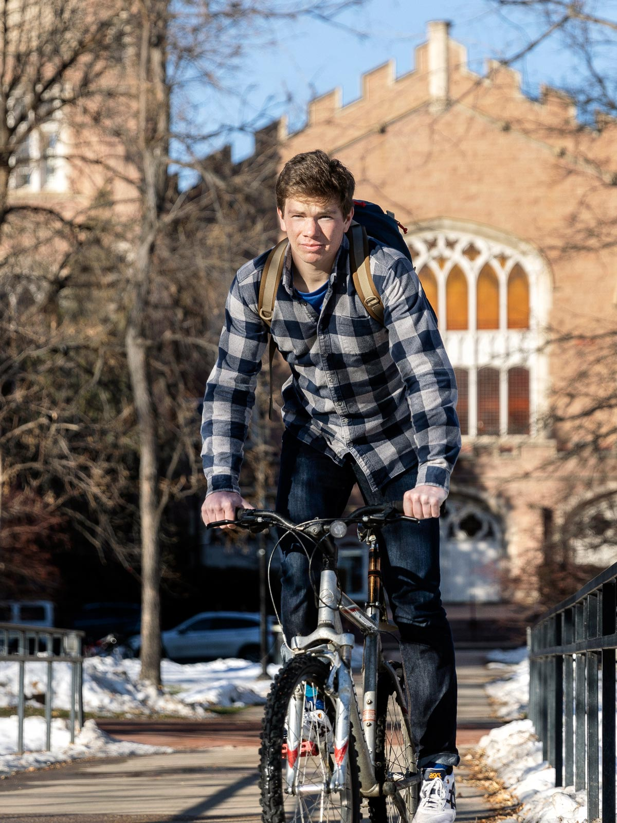 A young man on his bike riding in front of Macky Auditorium at the University of Colorado