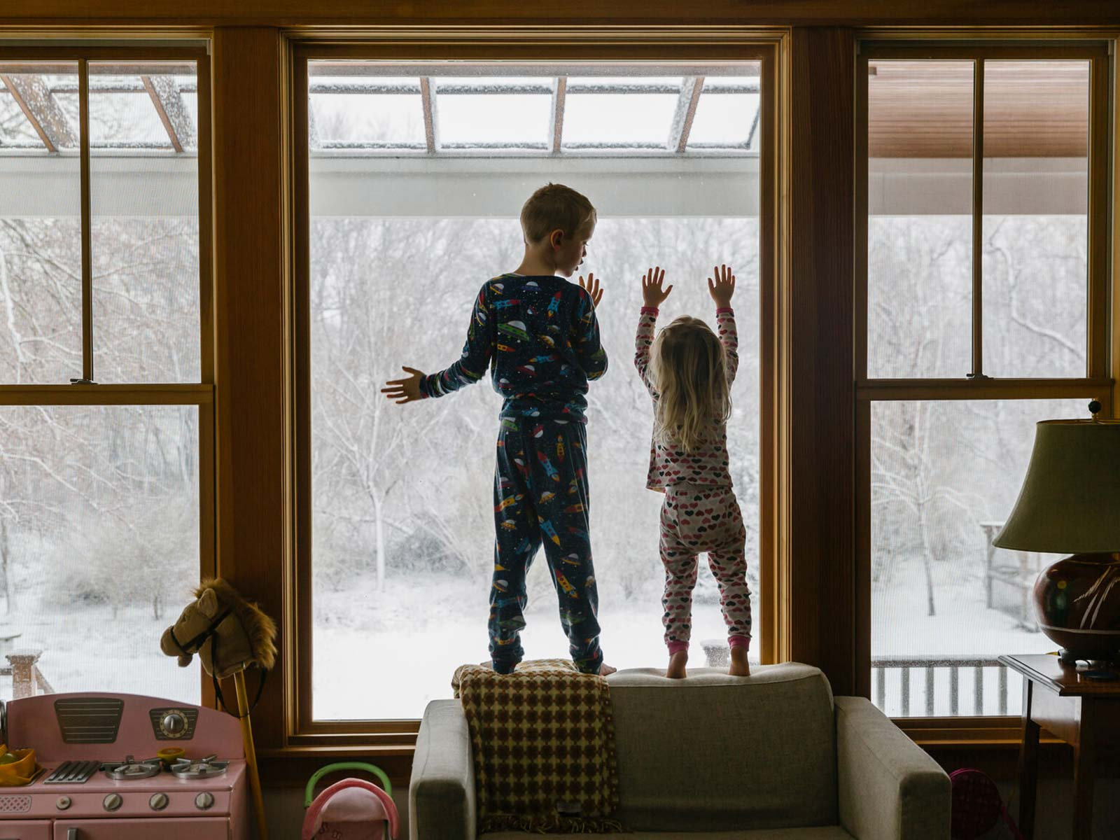 Two children standing on the window ledge in the living room, looking out the window as it snows