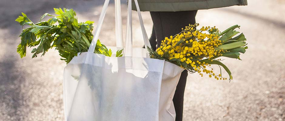 Cropped image of a canvas grocery bag filled with vegetables and flowers