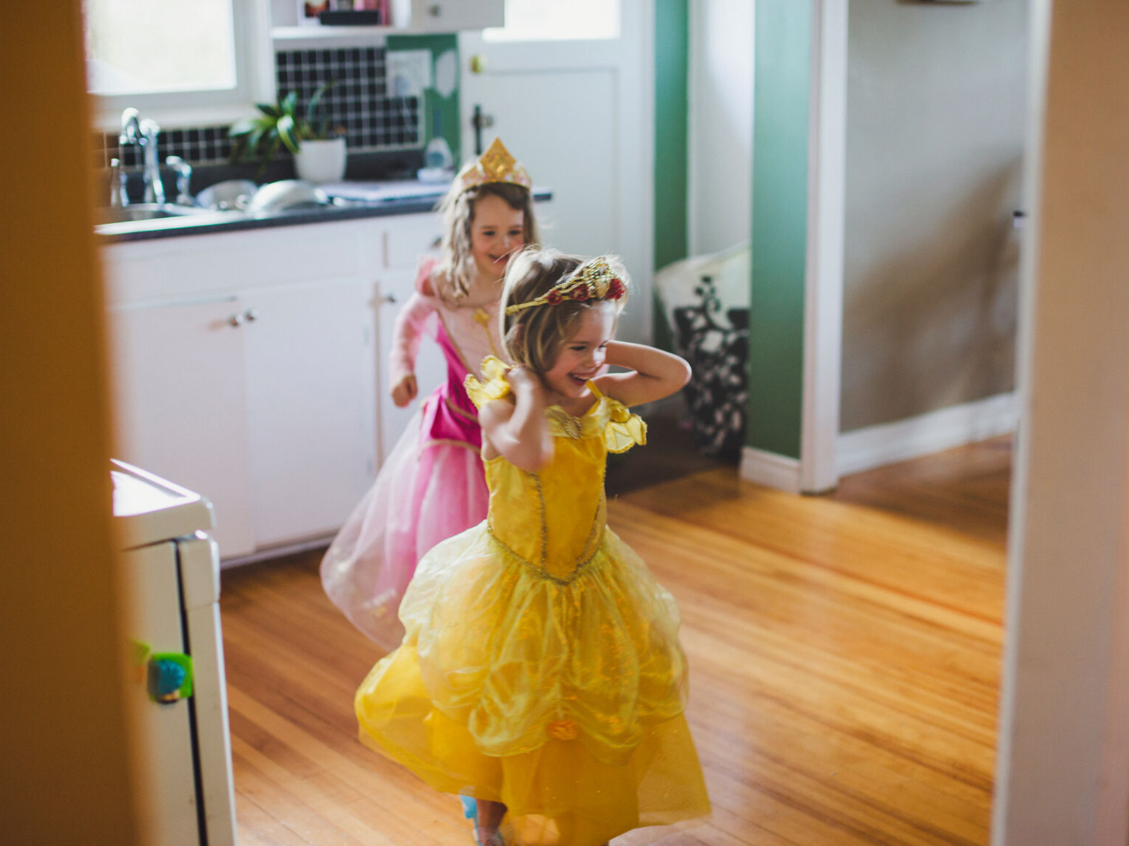 Two little girls wearing princess costumes play in the kitchen